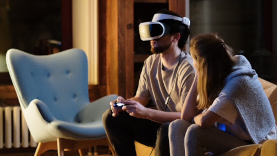 A couple sitting on a sofa, while the guy is wearing a VR headset enjoying extended reality