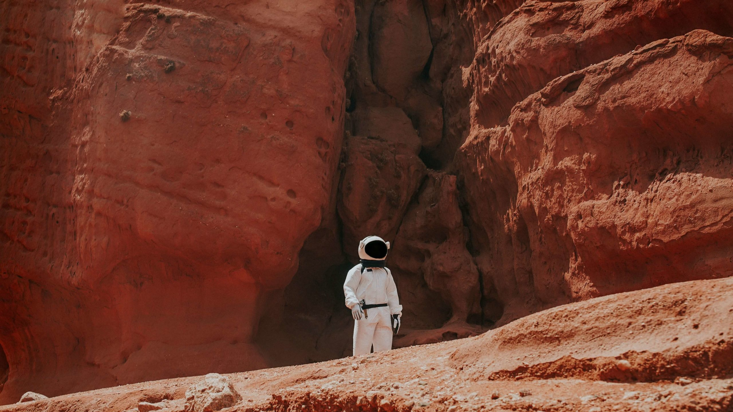 Astronomer standing by red stones. This is how it might look like when astronomers walk on Mars